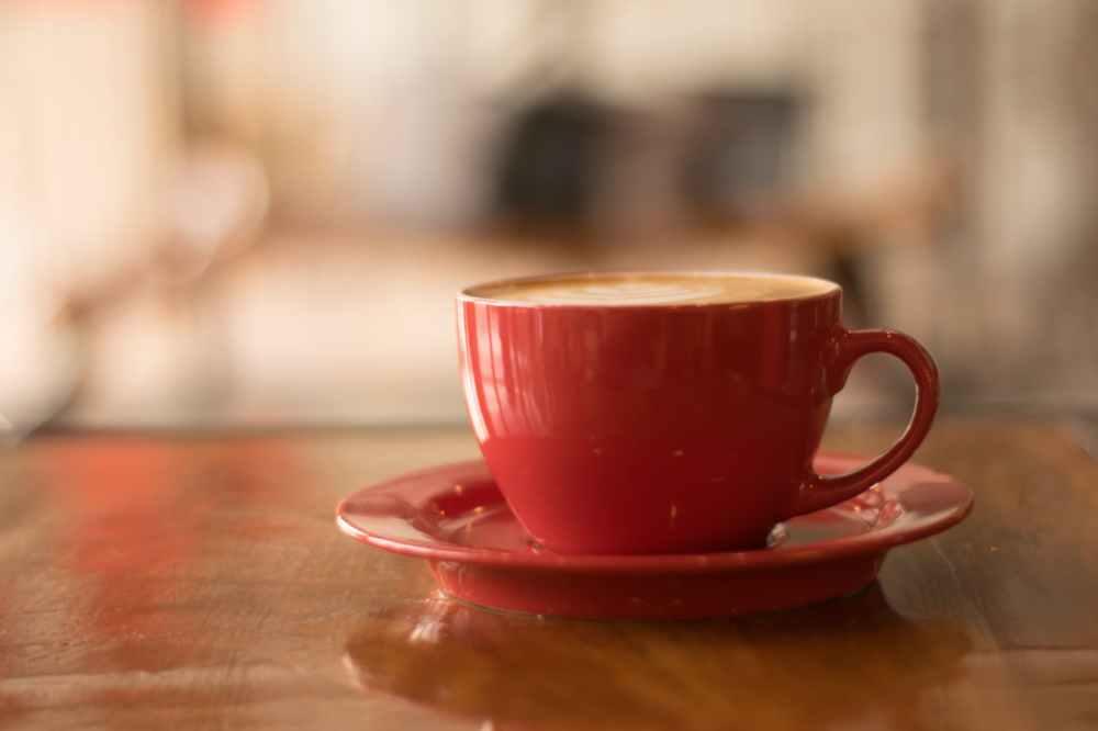 red ceramic mug on red saucer